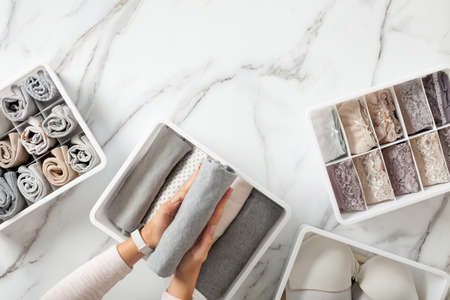 Woman hands neatly folding underwears and sorting in drawer organizers on white marble background. Archivio Fotografico
