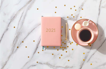 Notebook with empty pages for text, with pen, coffee cup, gift boxes, gold sparkles on white desk