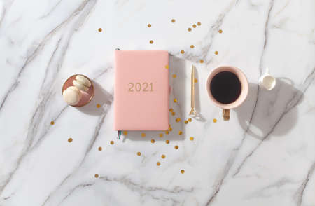 Pink coral colored diary for the year 2021, pen, coffee, macaron cookie. Marble background