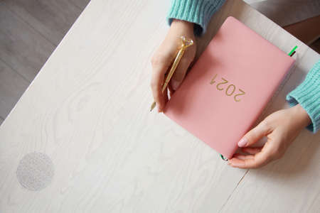 Woman sitting in knitted warm sweater with coral coloured 2021 diary on table
