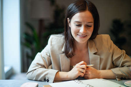 Beautiful young woman in suit writing her business plans while drinking coffee on break time