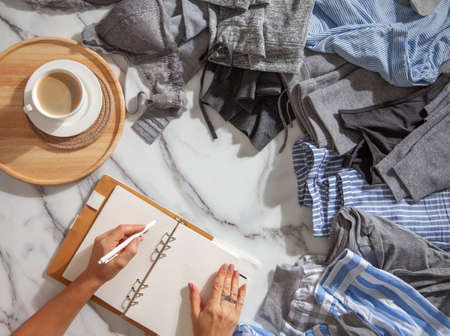Woman is making daily to do list and schedule on notebook the organization of wardrobe in a closet.