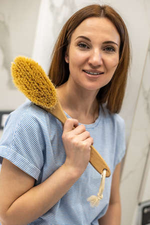 Young woman holding wooden brush and sitting near opened drawer with well organized bath amenities.