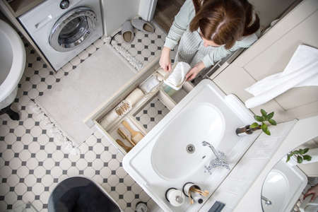 Housewife hands putting rolled up towel into drawer under sink. Organizing storage space in bathroom
