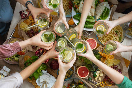 Top view closeup female friends hands cheers toasting glass of healthy beverage over serving table Standard-Bild