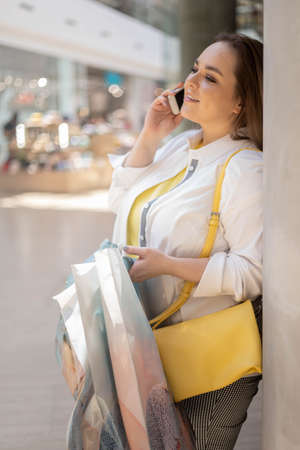 Closeup buyer woman talking smartphone smiling holding bags with purchasing at shopping mall Zdjęcie Seryjne