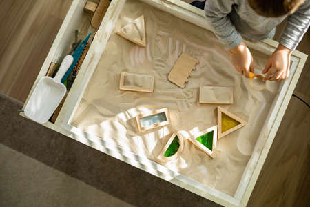 A woman is cleaning up her white workplace. Neatly arranged gold stationery. Storage method.