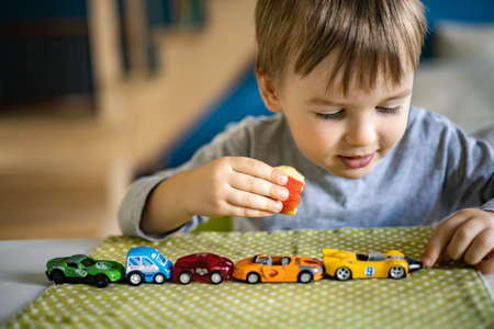 Little boy plays with toy cars while sitting at the table. Laughs and enjoys his toys. Imagens