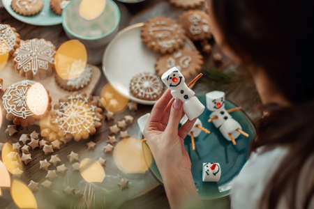 Mom and children decorate Christmas gingerbread at home. A boy and a girl paint with cornets with sugar icing on cookies. New Years decor, branches of a Christmas tree.