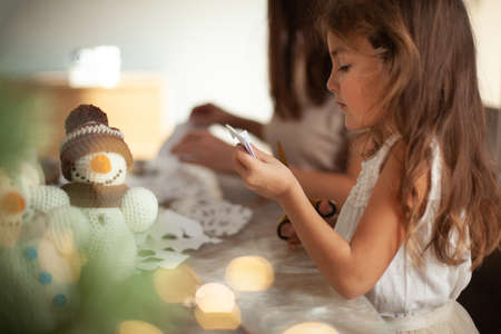 Little cute girl cuts snowflakes from white paper. Gingerbread and cocoa with marshmallows. The concept of preparation for the New Year and Christmas.