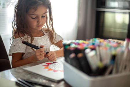 A little cute girl draws a circular mandala pattern in the album with art markers.