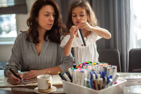 Young beautiful mother and cute daughter draw a mandala pattern together. Artistic markers and colored pencils. Imagens