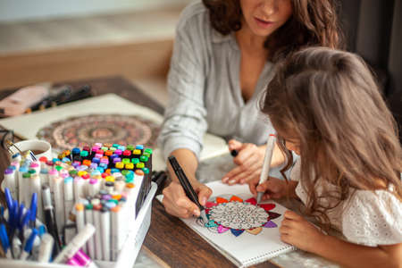 Young beautiful mother helps her daughter to draw a big flower in the style of zen drawing. Circular mandala. Imagens