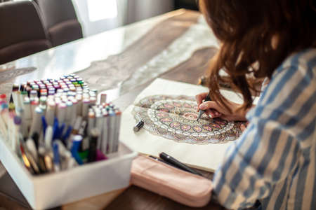 Young beautiful woman is sitting in the home kitchen and drawing a coloring mandala. Zen drawing.