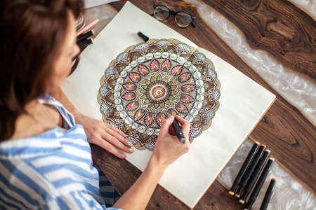 Young beautiful girl with long hair draws a circular mandala pattern. Imagens