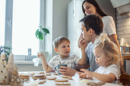 Dad, mom and children decorate Christmas gingerbread at home. A boy and a girl paint with cornets with sugar icing on cookies. New Years decor, branches of a Christmas tree.