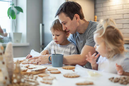 Dad and children decorate Christmas gingerbread at home. A boy and a girl paint with cornets with sugar icing on cookies. New Years decor, branches of a Christmas tree.