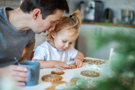 Dad and daughter decorate Christmas gingerbread at home. A boy and a girl paint with cornets with sugar icing on cookies. New Years decor, branches of a Christmas tree.