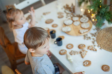 Boy and girl decorate Christmas gingerbread at home. A boy and a girl paint with cornets with sugar icing on cookies. New Years decor, branches of a Christmas tree. Imagens