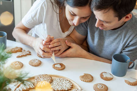 Beautiful man and woman decorate Christmas gingerbread. Two people draw a heart on the cookie. Stylish home kitchen