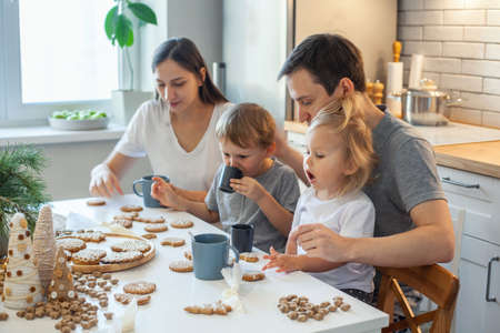 A cheerful family decorates Christmas gingerbread, drinks tea and has fun. Stylish home kitchen. Imagens