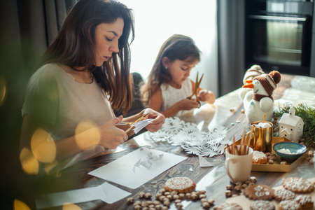 Little cute girl and young beautiful woman cut snowflakes from white paper. Gingerbread and cocoa with marshmallows.