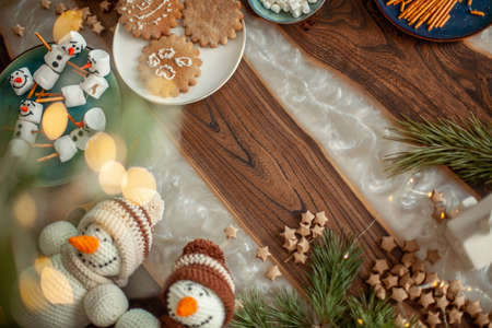Topview table with Christmas decor. Snowmen from marshmallows decorated with sugar glaze. Gingerbread cookies in the form of snowflakes. Imagens