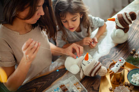 Little cute girl and young beautiful woman make knitted snowmen. Mom and daughter are sewing on buttons. Imagens