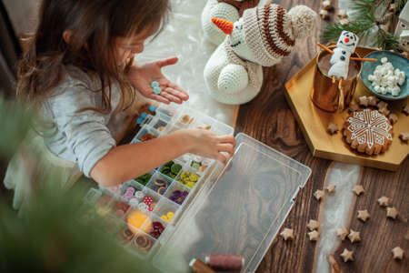 Little cute girl chooses buttons for knitted snowmen. New Years decor is on the table. Preparation for Christmas concept.