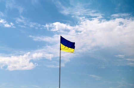 Flag of Ukraine with flag pole waving in the wind on front of blue sky