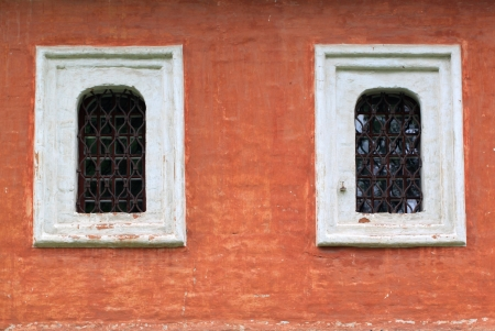 Two windows with bars on the red wall Stock Photo - 22027963