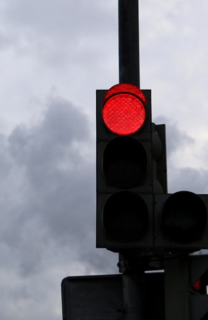 red light is photographed close up against a gray sky photo