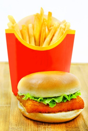 delicious food: Burger with fries and fish is photographed close-up on a wooden board Stock Photo