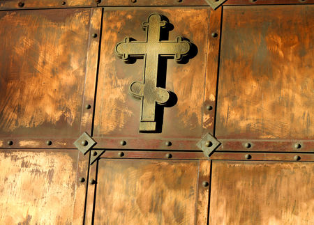 horse pipes: The copper cross on the gate, photographed close up
