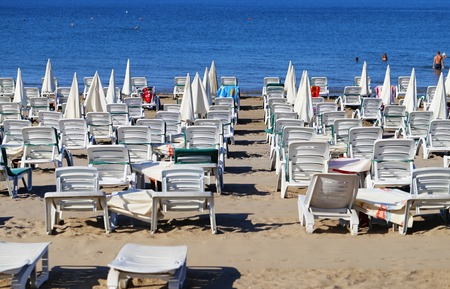 loungers: Beautiful sun loungers with parasols on the beach Stock Photo