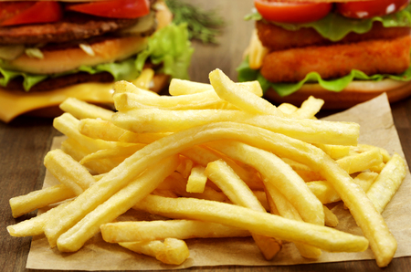 French fries photographed closeup on a background of delicious burgers with meat