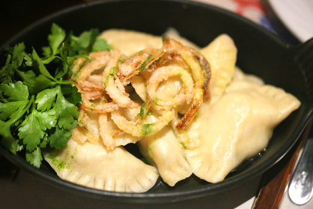 Delicious dumplings with cheese and onions in a bowl
