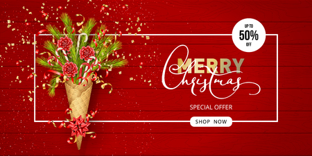 Merry Christmas and Happy New Year composition in a waffle cone of coniferous branches. Festive Christmas tree decorations on wooden red background. Christmas sale banner