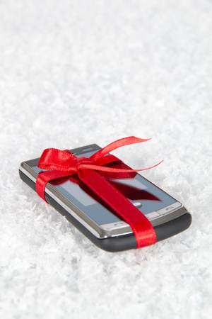 Mobile phone in a gift by a holiday photo