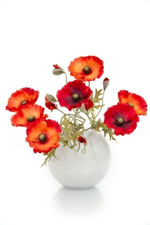 poppies: The image of a bouquet of artificial poppies in a vase, isolated, on a white background.