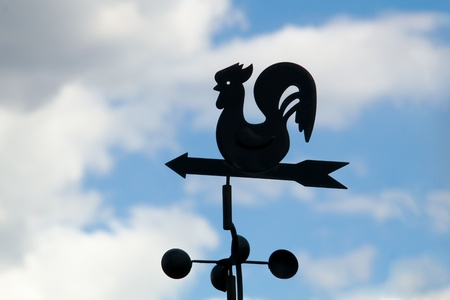 Weather vane on a backgrounds a cloudy sky