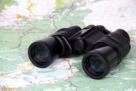 cartographer: Black binoculars lies on the a geographical map Stock Photo