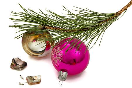 Broken Christmas ball lies beneath branch of the pine, isolated on a white background