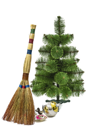 Balayage of broken Christmas decorations with the help of a besom, on a Christmas tree background, isolated on white