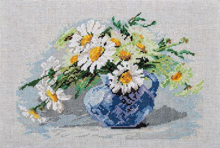Embroidered picture, still life with bouquet of flowers in vase, cross-stitch on textile canvas, isolated on white background