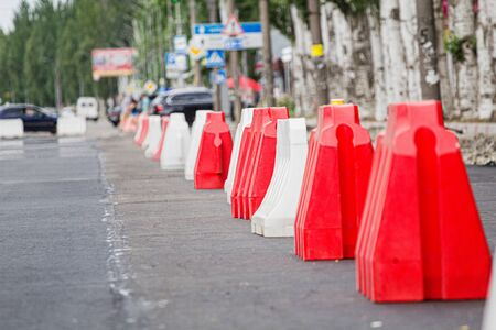 Red and white plastic barriers blocking the road for the time of repair work on the replacement of asphalt, road repair in the street in the city