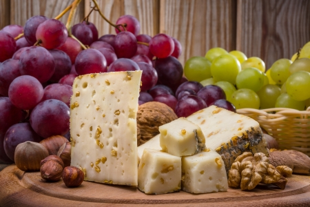 cheese and grapes on wood background photo
