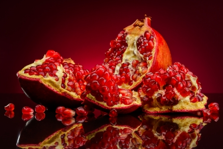 red pomegranate fruits on a dark background photo