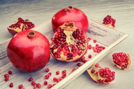 red pomegranate fruits on a white vintage background photo