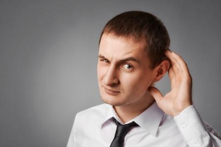 jeune homme d'affaires curieux europian essaie d'écouter